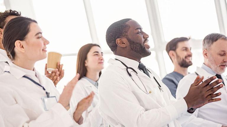 Gruppe von Menschen in weißen Kitteln, teilweise mit Stetoskop, applaudiert.