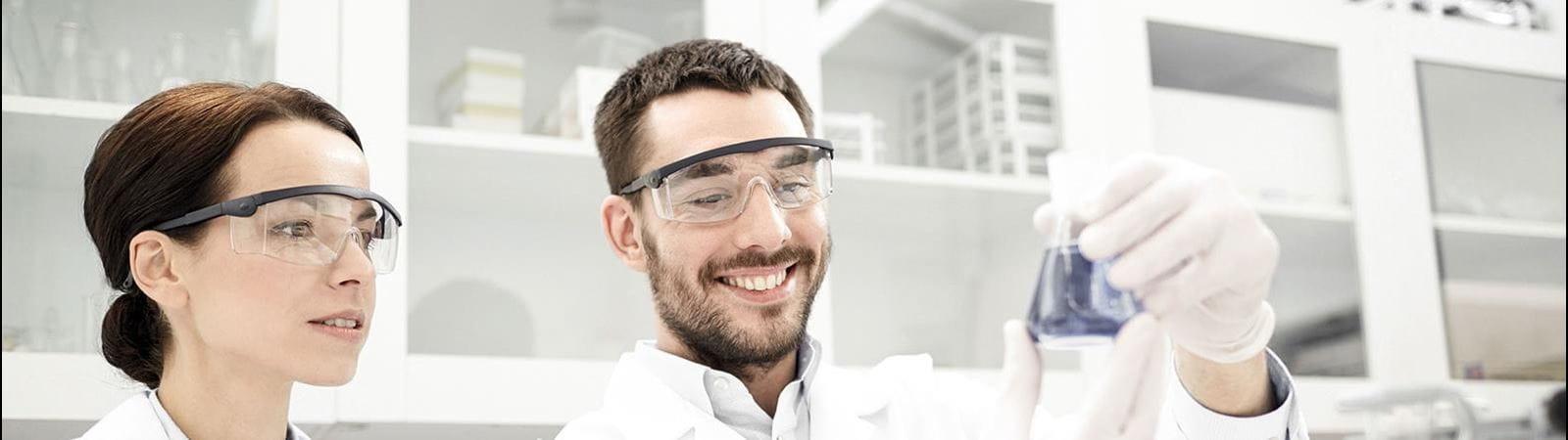 Mann und Frau in Labor betrachten Fläschchen.